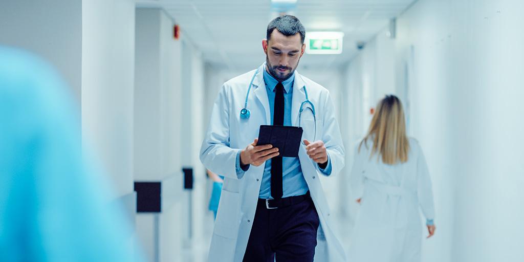 Doctor on ipad walking hospital hallway